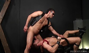 Alexander is standing alone in a dungeon room wearing leathe...