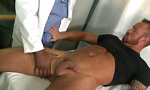 Doctor Adonis comes into the room and begins to check Michael`s muscles out. He has him lay out on the exam table and spread his legs. He begins to rub Michael`s thighs and inner as well. Michael notices that his Doc has become aroused and his hard cock i